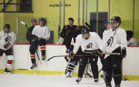 Senior Ryan Sexton and junior Matt Tuccunardi take the ice during practice while senior Andrew Kydes and freshman Shane Sexton look on from the boards.