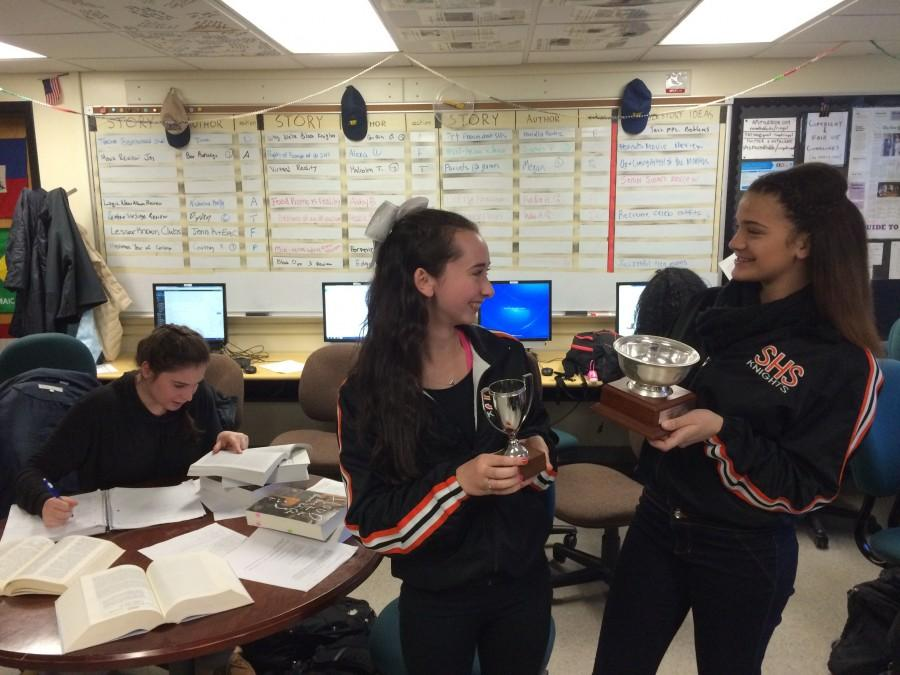 In this staged photo, junior Mariel Barocas studies hard as cheerleaders Ivory McCulley and Jessica Torrellas celebrate their victories.