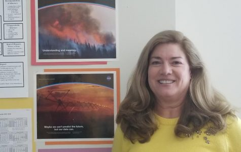 Science Teacher Sue Dougherty poses next to NASA artwork in her SHS classroom.