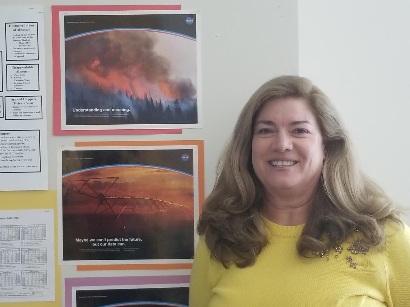 Science Teacher Sue Dougherty poses next to NASA artwork in her SHS classroom.