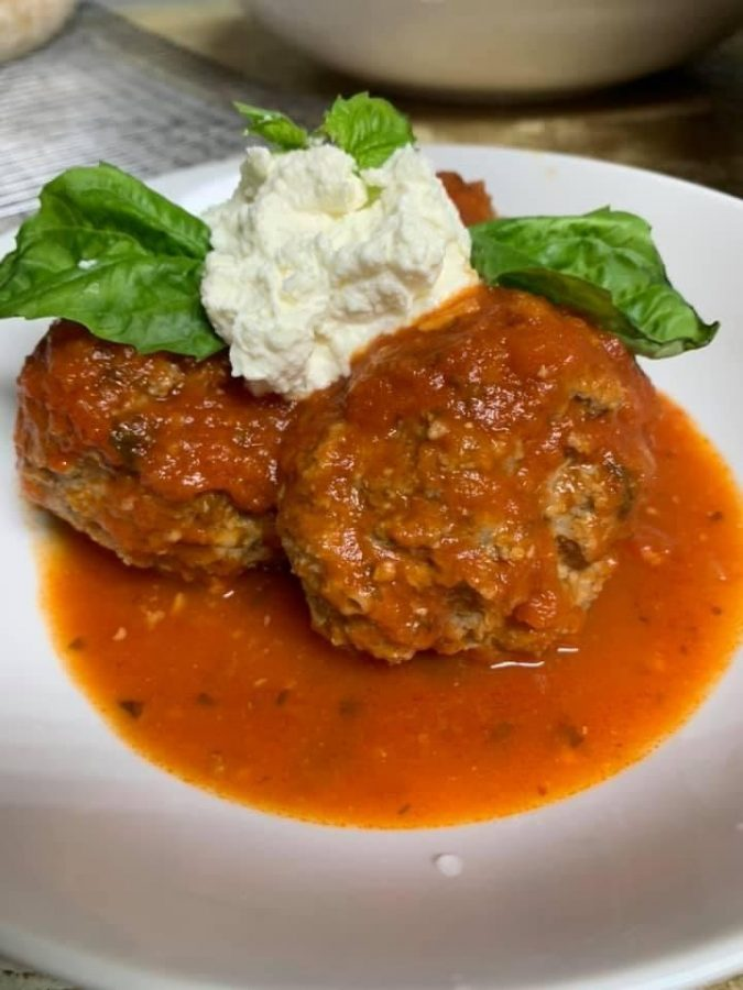 Nonna special with homage meatballs in sauce and homemade ricotta topped with basil leaves.