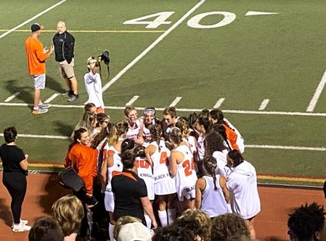 Field hockey team huddles during time out